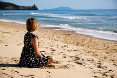 Donna attraente che si siede su un litorale di mare Fotografia Stock Libera da Diritti