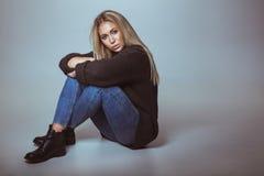 Donna attraente che si siede sul pavimento Fotografia Stock Libera da Diritti