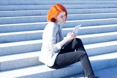 Donna attraente che si siede sulle scale sulla via e che lavora ad una compressa Immagini Stock Libere da Diritti