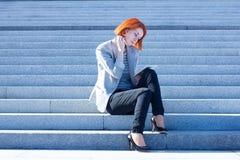 Donna attraente che si siede sulle scale sulla via e che lavora ad una compressa Fotografia Stock Libera da Diritti