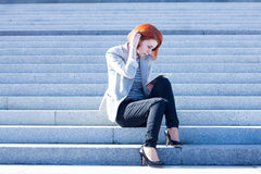 Donna attraente che si siede sulle scale sulla via e che lavora ad una compressa Immagini Stock