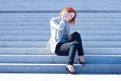 Donna attraente che si siede sulle scale sulla via e che lavora ad una compressa Immagine Stock