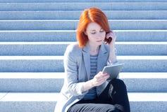 Donna attraente che si siede sulle scale sulla via e che lavora ad una compressa Fotografie Stock
