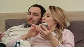 Donna attraente che si trova a letto mandando un sms al telefono cellulare che sorride, mentre la sua leva del partner allo scher video d archivio