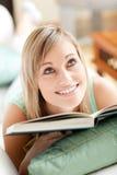 Donna attraente che si trova su un sofà che legge un libro Immagini Stock