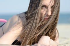 Donna attraente che si trova sul bikini di usura della sabbia Fotografie Stock