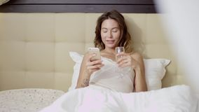 Donna attraente che si trova sul letto con un vetro di champagne e di uno smartphone archivi video