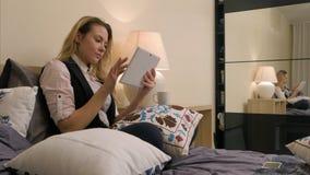 Donna attraente che si trova sul letto facendo uso della compressa digitale Fotografia Stock