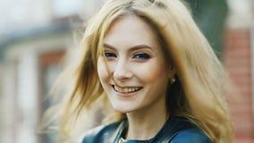 Donna attraente che sorride alla macchina fotografica, giocante con i suoi capelli video d archivio