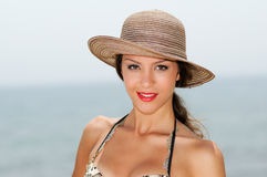 Donna attraente che sorride con un cappello del sole su una spiaggia tropicale Fotografia Stock