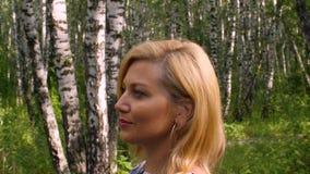 Donna attraente che sorride e che cammina nel boschetto della betulla nel parco di estate Vista di profilo archivi video