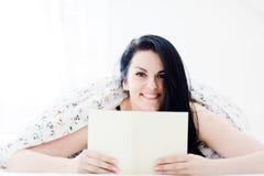 Donna attraente che sorride, rilassantesi e libro di lettura in camera da letto immagine stock
