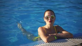 Donna attraente che sta dal lato della piscina e che gode della vacanza stock footage