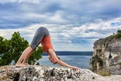 Donna attraente che sta sulla roccia e che fa gli esercizi di yoga sopra il fiume Immagini Stock