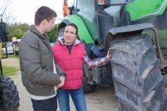 Donna attraente che vende trattore nuovissimo all'agricoltore del principiante fotografie stock
