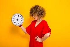 Donna attraente con brevi capelli ricci con gli orologi fotografie stock