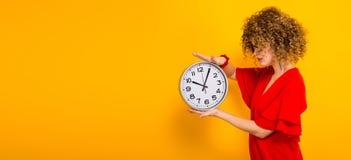 Donna attraente con brevi capelli ricci con gli orologi fotografia stock