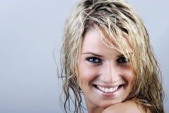 Donna attraente con capelli bagnati che sorride alla macchina fotografica fotografia stock libera da diritti