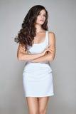 Donna attraente con capelli ricci in breve vestito bianco Fotografie Stock