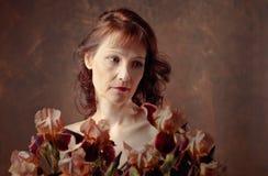 Donna attraente con i fiori marroni dell'iride fotografia stock libera da diritti