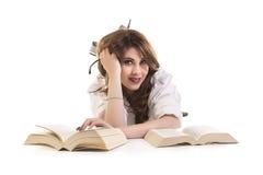 Donna attraente con i libri che si trovano sul pavimento Fotografia Stock