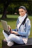 Donna attraente con il computer portatile e il sandwitch Immagini Stock
