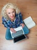 Donna attraente con il computer portatile ed il libro Immagini Stock