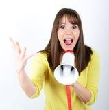 Donna attraente con il megafono contro fondo bianco Fotografie Stock Libere da Diritti