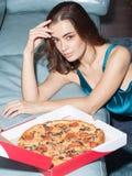 Donna attraente con il pezzo della pizza fotografie stock