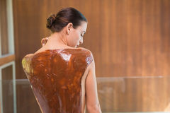 Donna attraente con la maschera della parte posteriore del cioccolato al centro della stazione termale Fotografie Stock