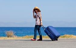 Donna attraente con la valigia sulla spiaggia fotografie stock libere da diritti