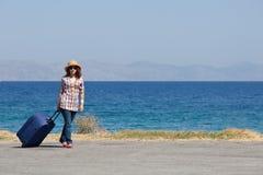 Donna attraente con la valigia sulla spiaggia immagini stock