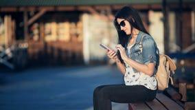Donna attraente con lo Smart Phone che scrive un messaggio di testo a macchina in un caffè della via stock footage