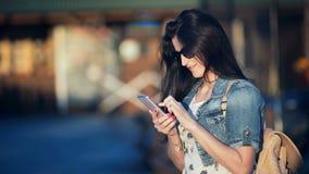 Donna attraente con lo Smart Phone che scrive un messaggio di testo a macchina in un caffè della via video d archivio