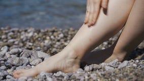 Donna attraente con pelle sana che si applica protezione solare alle gambe archivi video
