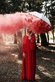 Donna attraente con un modo variopinto della bomba della granata fumogena fotografia stock