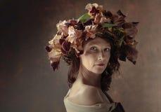 Donna attraente in corona con i fiori marroni dell'iride immagini stock libere da diritti