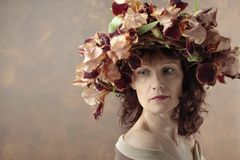 Donna attraente in corona con i fiori marroni dell'iride fotografie stock libere da diritti