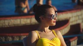 Donna attraente in costume da bagno ed occhiali da sole gialli che gode della ricreazione stock footage