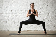 Donna attraente dei giovani Yogi nella posa della dea, backgrou bianco del sottotetto fotografie stock