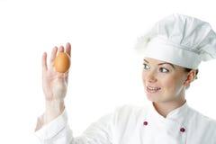 Donna attraente del cuoco con l'uovo Fotografia Stock