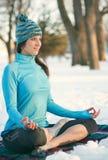Donna attraente della corsa mista che fa yoga in natura all'orario invernale Fotografie Stock