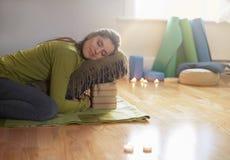 Donna attraente della corsa mista che fa yoga ristoratrice Immagini Stock