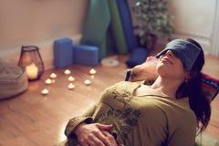Donna attraente della corsa mista che fa yoga ristoratrice Immagine Stock