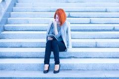 Donna attraente della testarossa che si siede sulle scale che leggono qualcosa con una compressa Immagini Stock