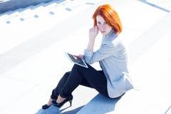 Donna attraente della testarossa che si siede sulle scale e che legge qualcosa con una compressa al giorno soleggiato Fotografie Stock