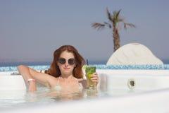 Donna attraente della testarossa nello stagno con un cocktail fotografie stock libere da diritti