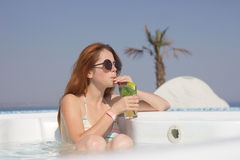Donna attraente della testarossa nello stagno con un cocktail fotografia stock libera da diritti
