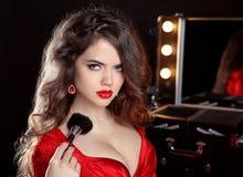 Donna attraente dello stilista di bellezza nel rosso con la spazzola di trucco dentro per Immagine Stock Libera da Diritti