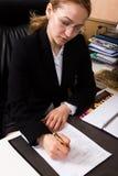 Donna attraente di affari che lavora con i documenti in ufficio donna in un vestito che si siede ad una tavola e ad un segno Immagine Stock Libera da Diritti